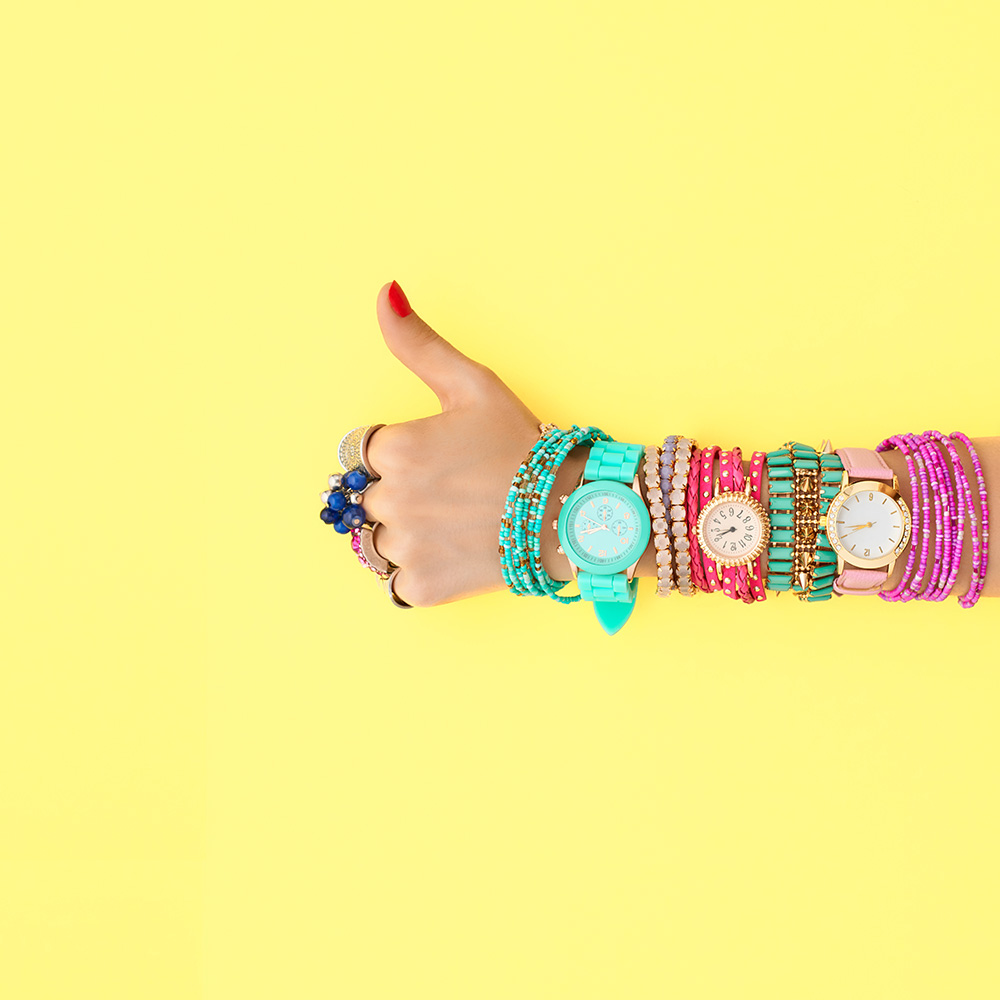 Closeup of woman wearing three colorful watches against yellow background giving a thumbs up.