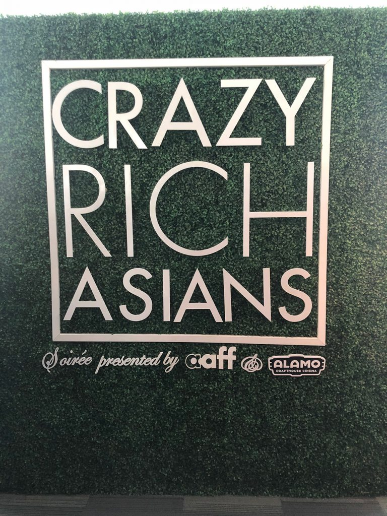 Crazy Rich Asians backdrop featuring sponsors.