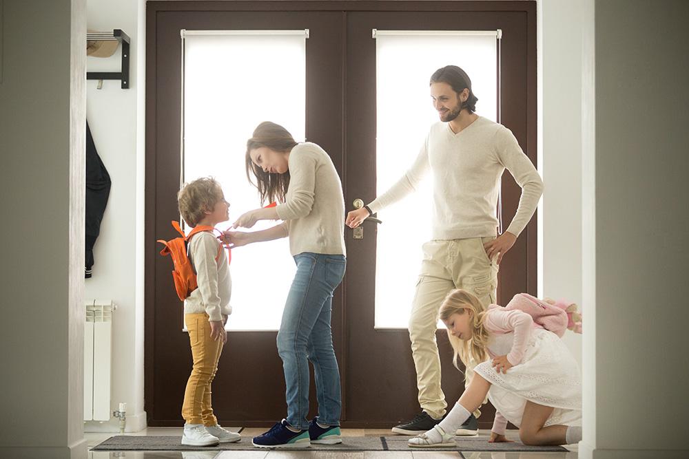 Parents preparing children for school by the front door.