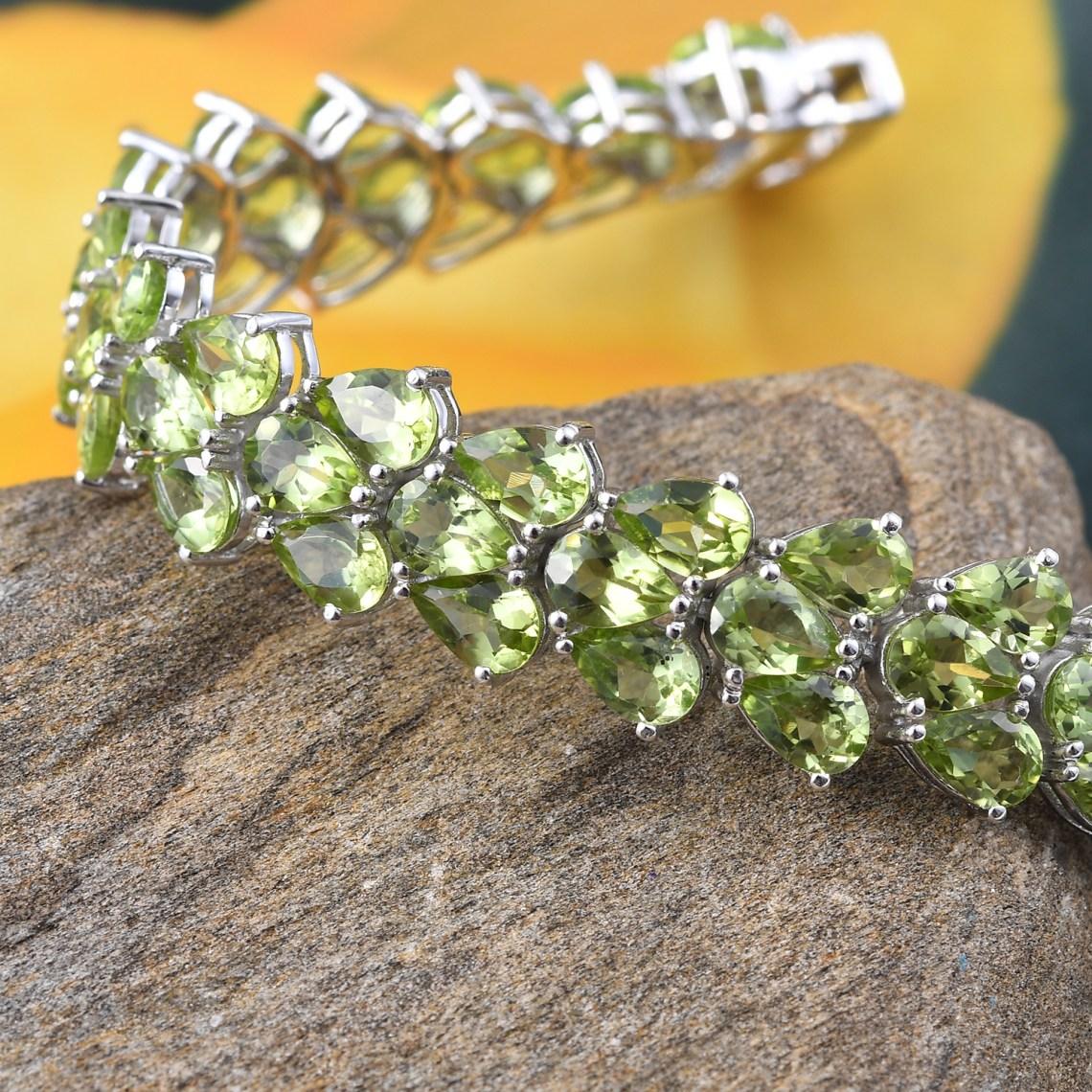 Peridot bracelet draped over stone.