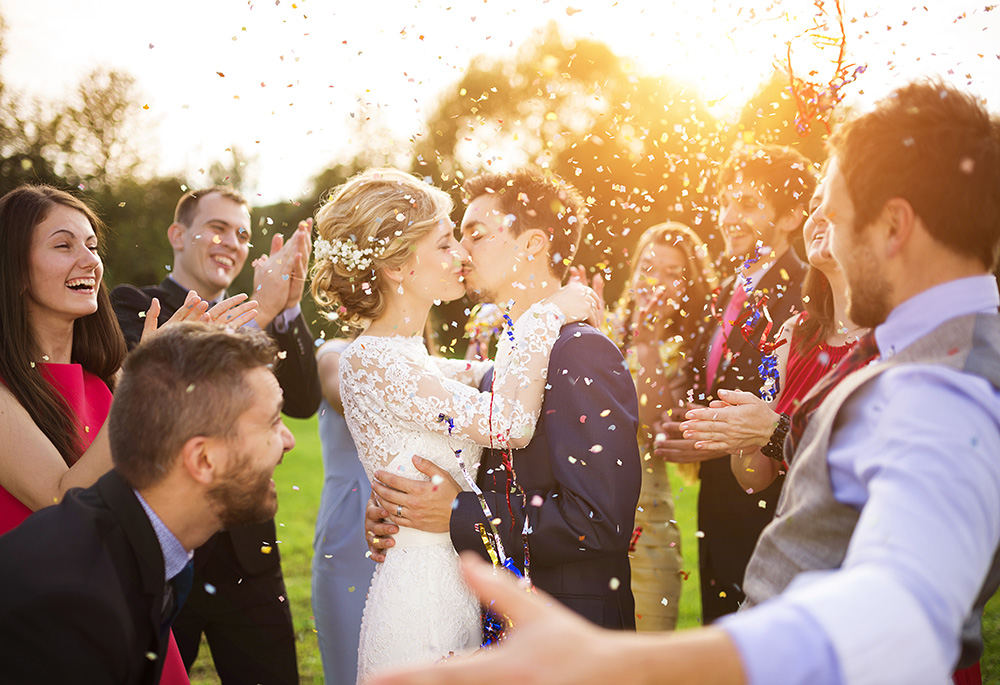 Couple kissing with guests congratulating them.