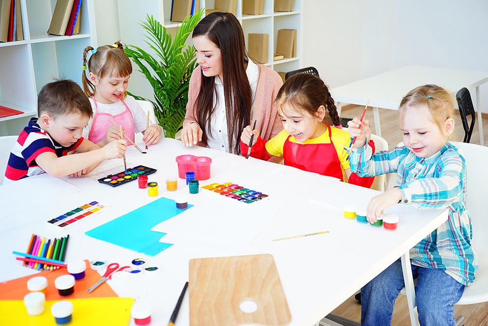 Teacher helping four children paint in a classroom.