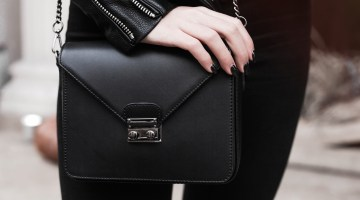 Closeup of woman with black nail polish clutching onto her black handbag in black outfits