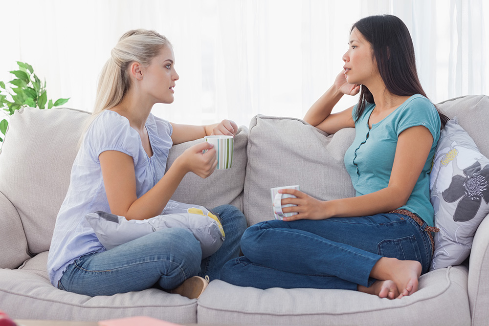 Two women talking about life on the couch with cups of tea.