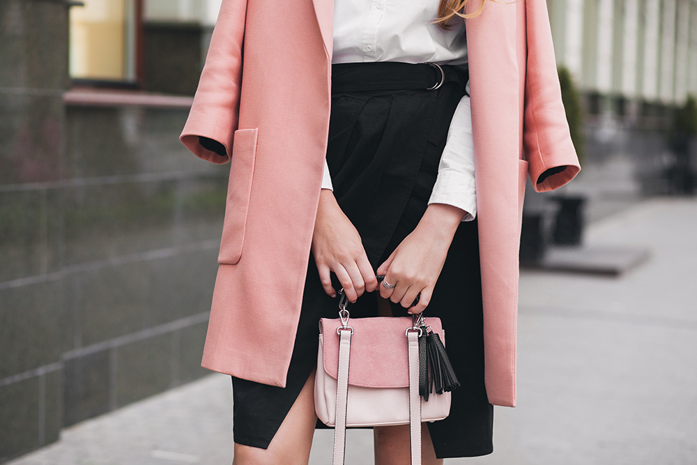 Woman wearing pink blazer and holding a pink purse against black form-fitting skirt