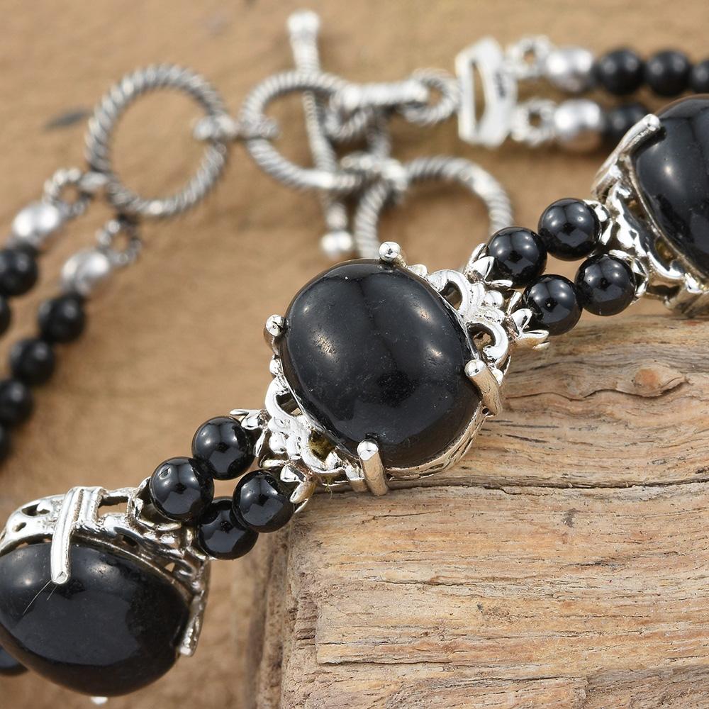 Black jade bracelet against wooden platform