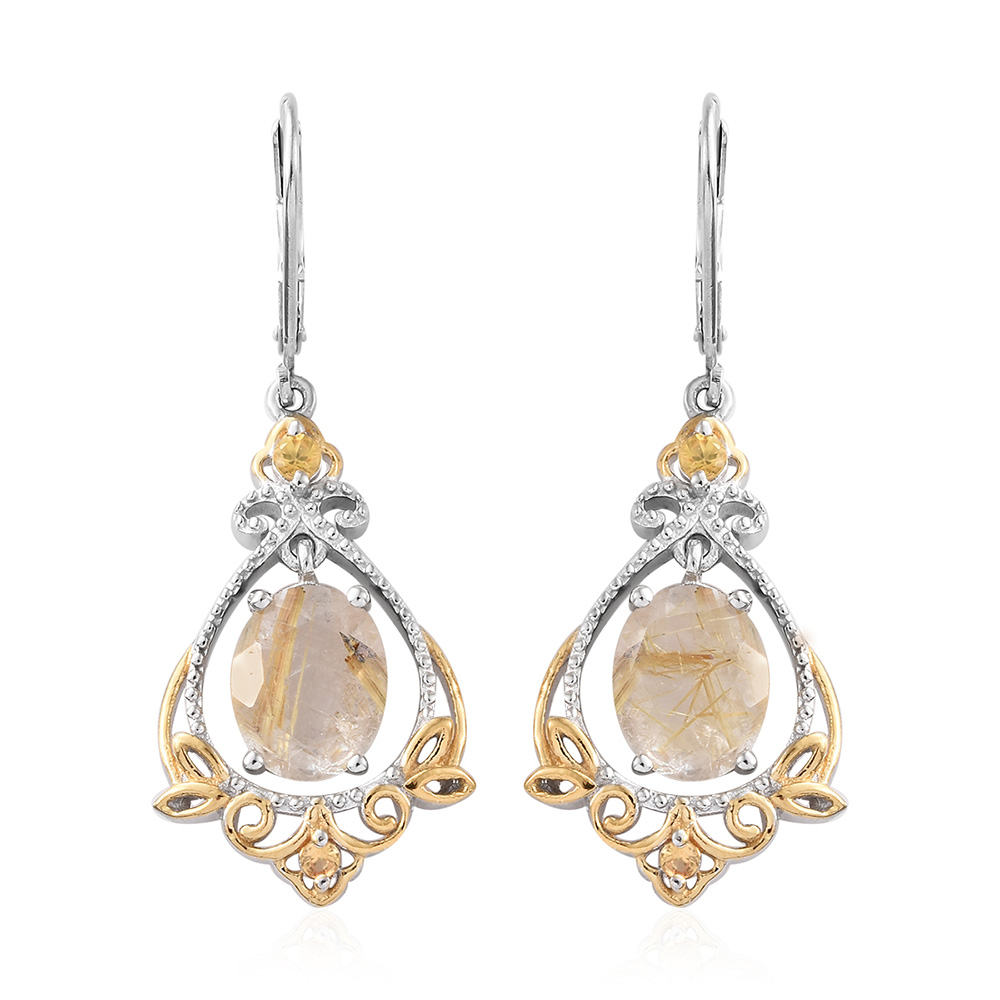 Closeup of yellow gold dangle earrings against white background