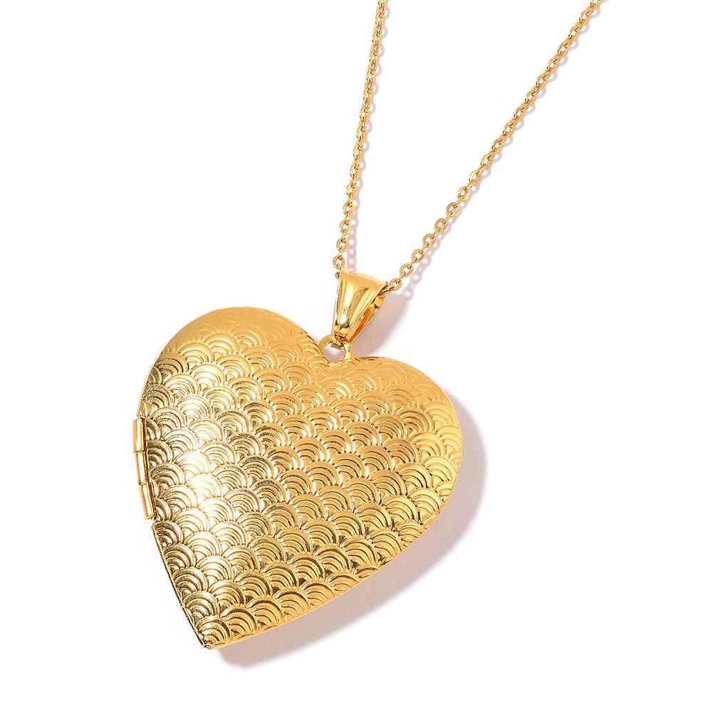 Closeup of gold heart necklace against white background