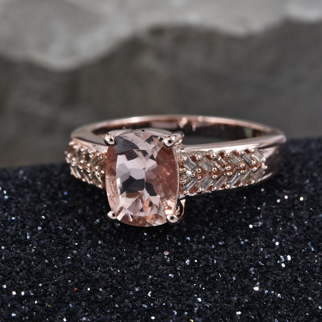 Morganite ring in rose gold on black sand.
