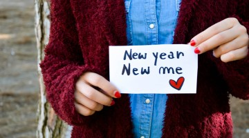 "Woman holding a ""new year, new me"" sign"