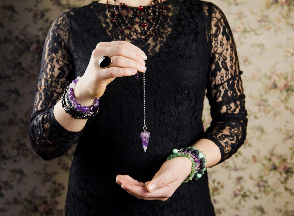 Woman in black dress dangling amethyst pendant.