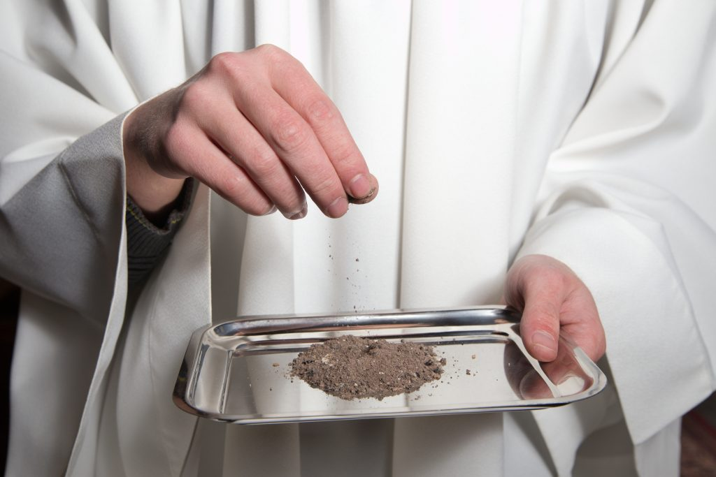 Priest in white preparing ashes for Ash Wednesday.