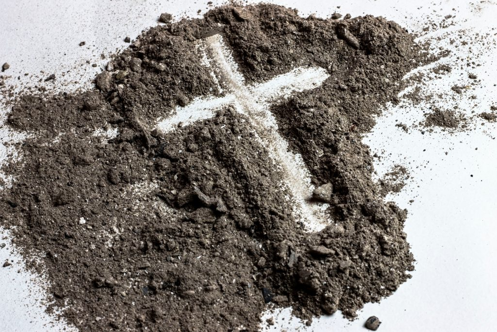 Pile of ashes with cross drawn through it.