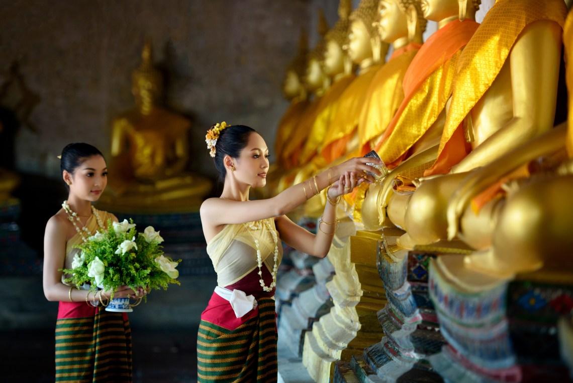 Cambodian women lighting incense in traditional ritual.