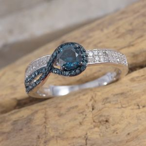 Blue diamond ring in silver on wood background.
