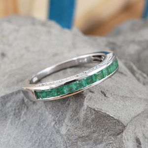 Band ring with channel set emerald gemstones on stone backdrop.
