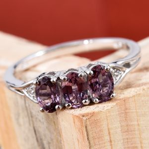 Lavender spinel three stone ring on wooden stand.