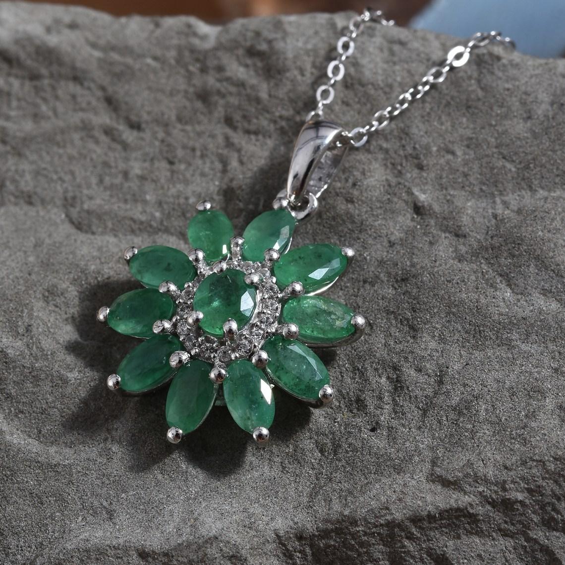 Emerald burst pendant displayed over gray stone background.