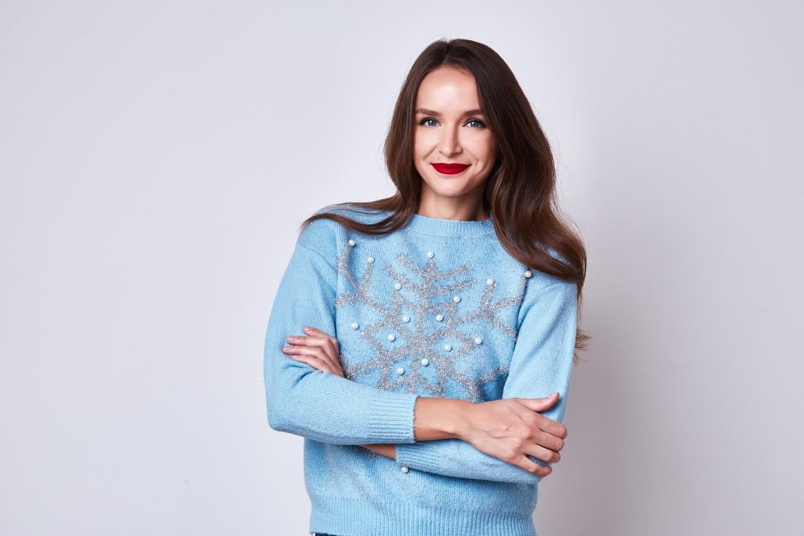 Woman wearing light blue DIY snowflake sweater.