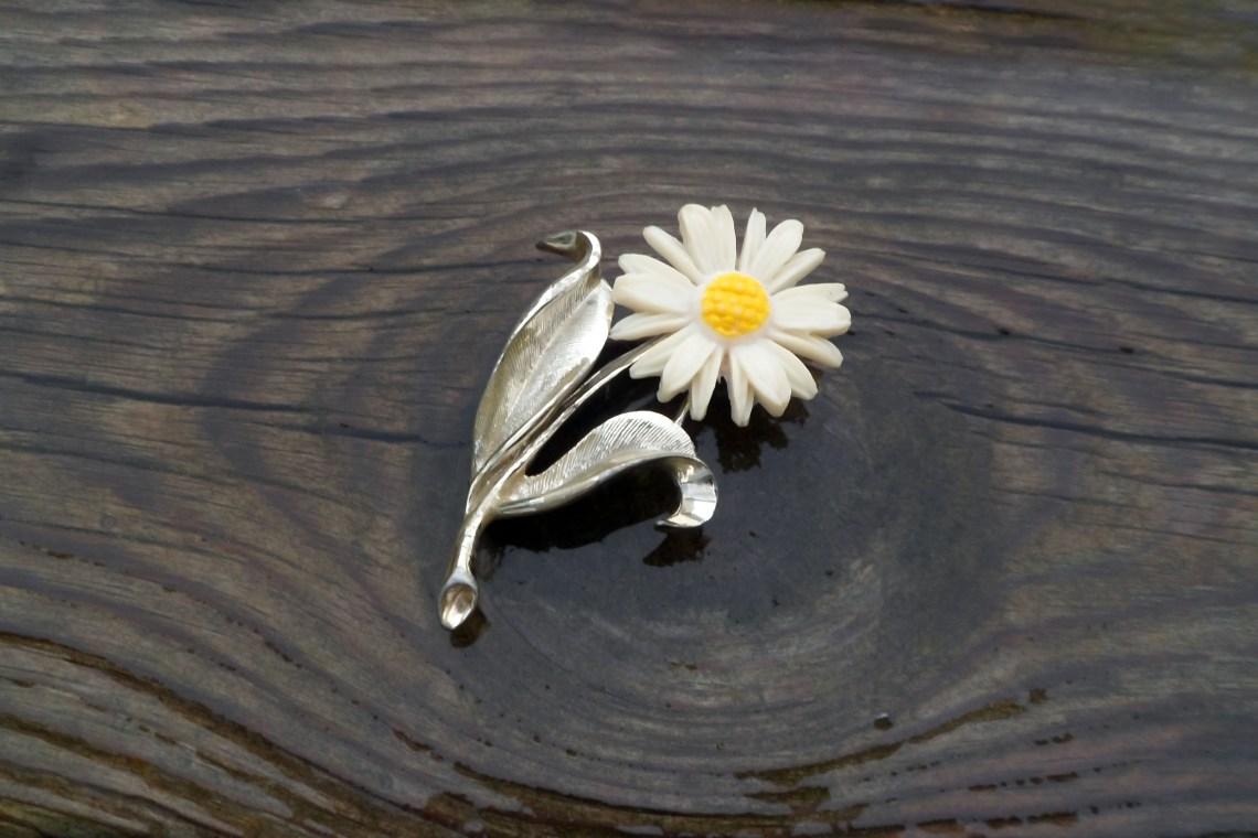 Vintage floral brooch on wood background.