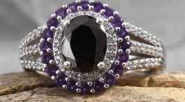 Shungite ring with amethyst halo resting on stone.