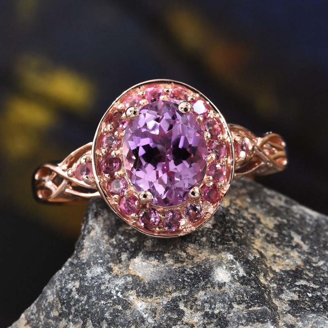 Kunzite ring in gold resting on stone.