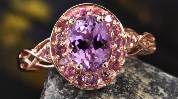 Kunzite ring in gold resting on stone.