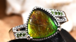 Ammolite ring in silver resting on black stone.