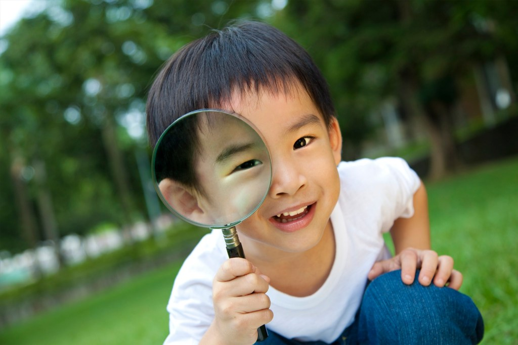 Happy kid with magnifying glass.