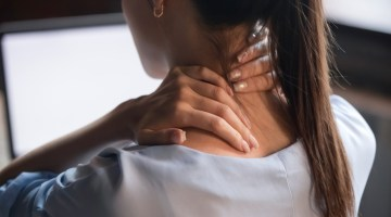Woman massaging sore neck.