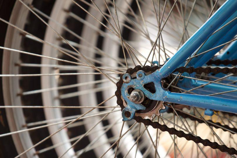 Plato de marchas y radio de una bicicleta azul, descuentos en ciclismo