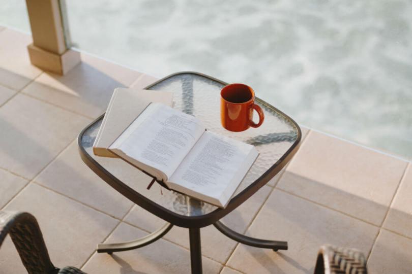 mesita junto a una piscina con libro y café