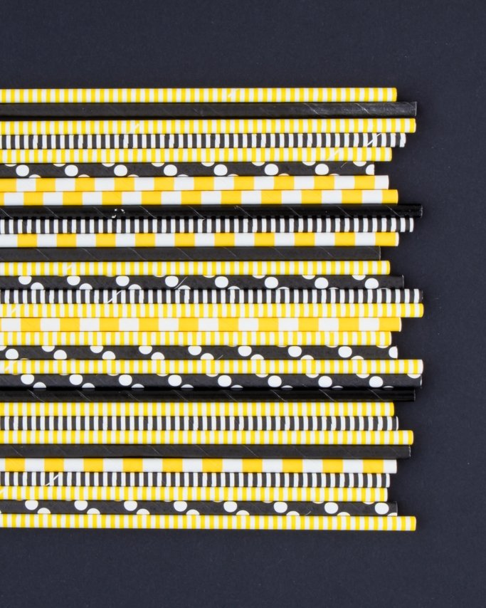 Bee Themed Party paper straws assorted yellow and black paper straws on black background