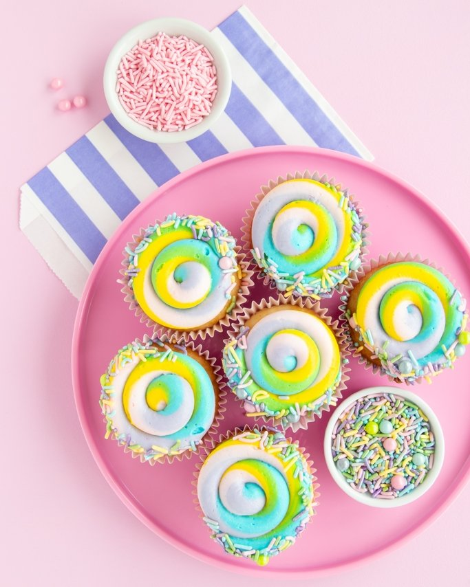 Pink plate full of pastel swirl cupcakes with Easter sprinkles on light pink background