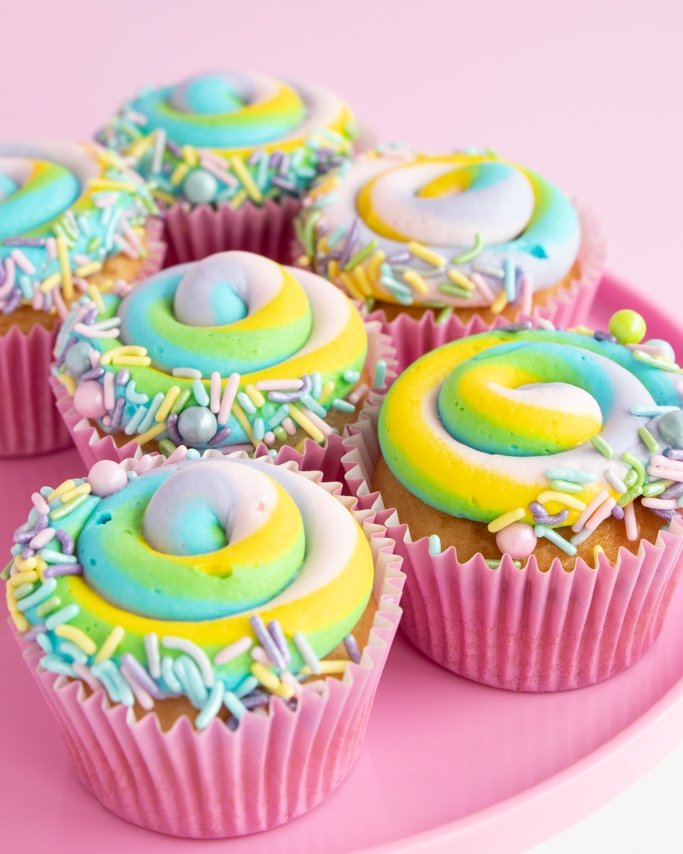 Pastel swirl Easter cupcakes with pastel sprinkles trim on pink plate and light pink background