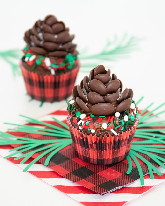 chocolate pine cone cupcake topper with lumberjack sprinkles and buffalo plaid cupcake liners