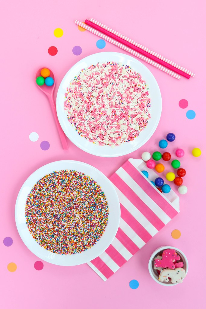 Circus Animal Cookies Party Ideas - White dishes filled with sprinkles and gumballs all around on a pink background.
