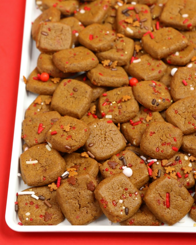 Gingerbread Cookie Bites with Reindeer Food Christmas Sprinkles on white server plate on red background