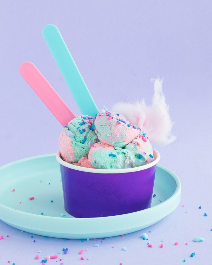 No Churn Cotton Candy Ice Cream in a purple ice cream cups with reusable ice cream spoons on blue plate