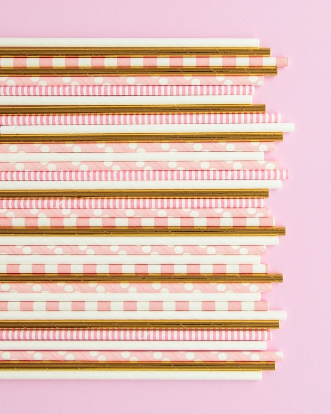 Pink and gold paper straws assortment on light pink background