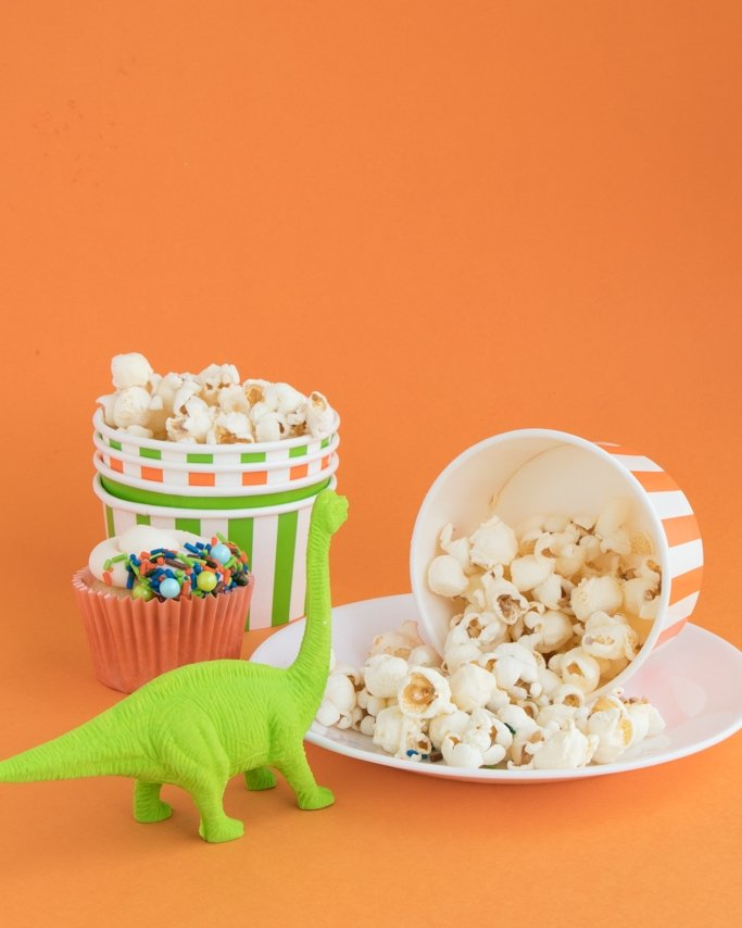 Dinosaur Party Ideas - Dino Popcorn on white plate and orange background