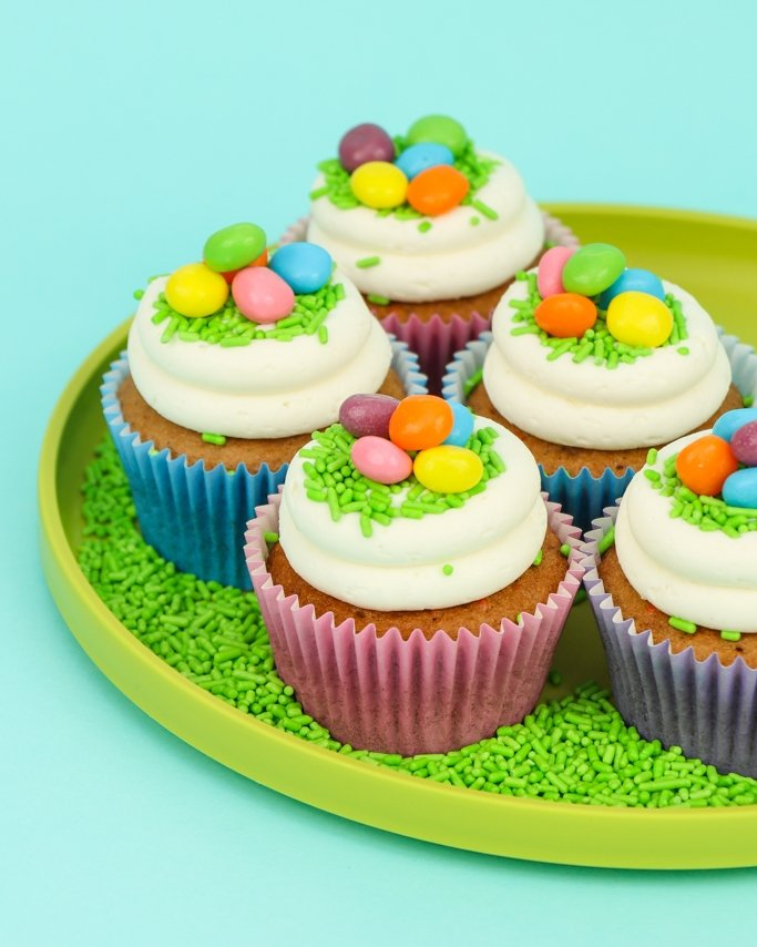 easter cupcakes with candy eggs on green tray