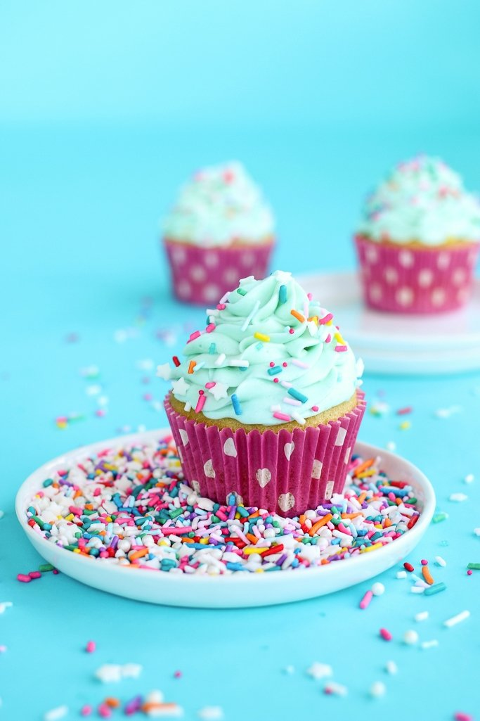 A cupcake decorated with birthday cake sprinkles and dot pink greaseproof cupcake liners
