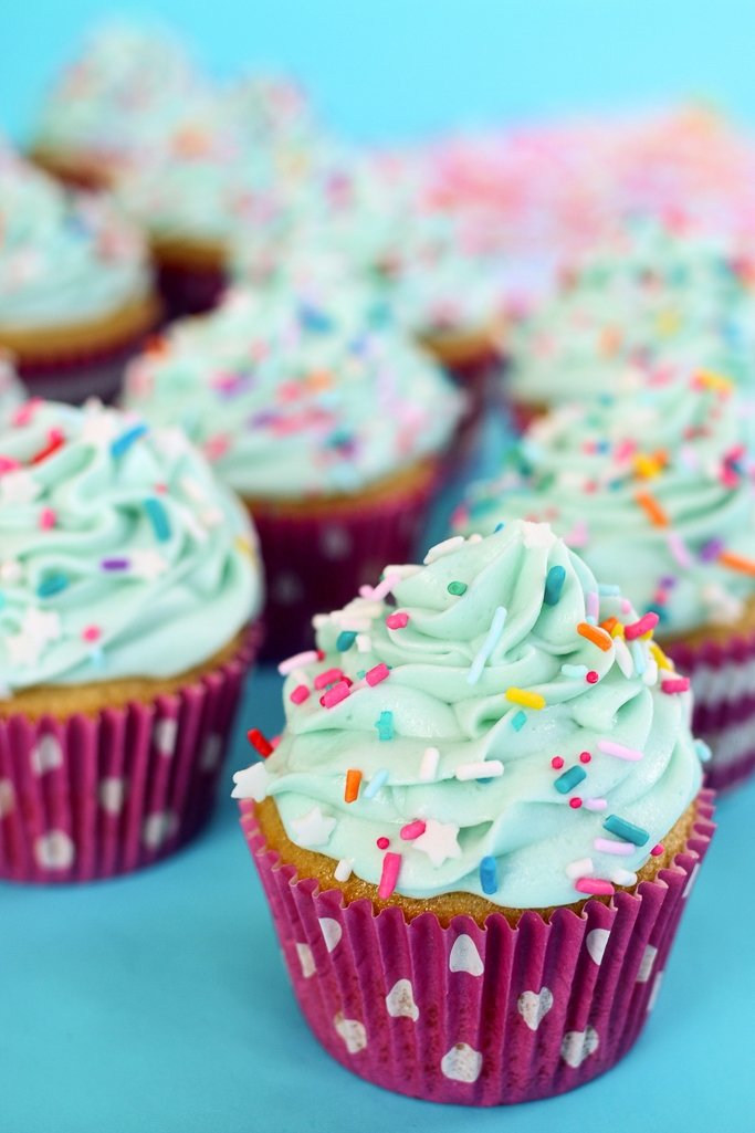 A group of vanilla cupcakes after they are decorated with light blue frosting and birthday cake rainbow sprinkles.