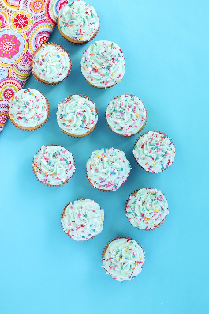 Overhead view of homemade vanilla cupcakes decorated with colorful birthday cake sprinkles