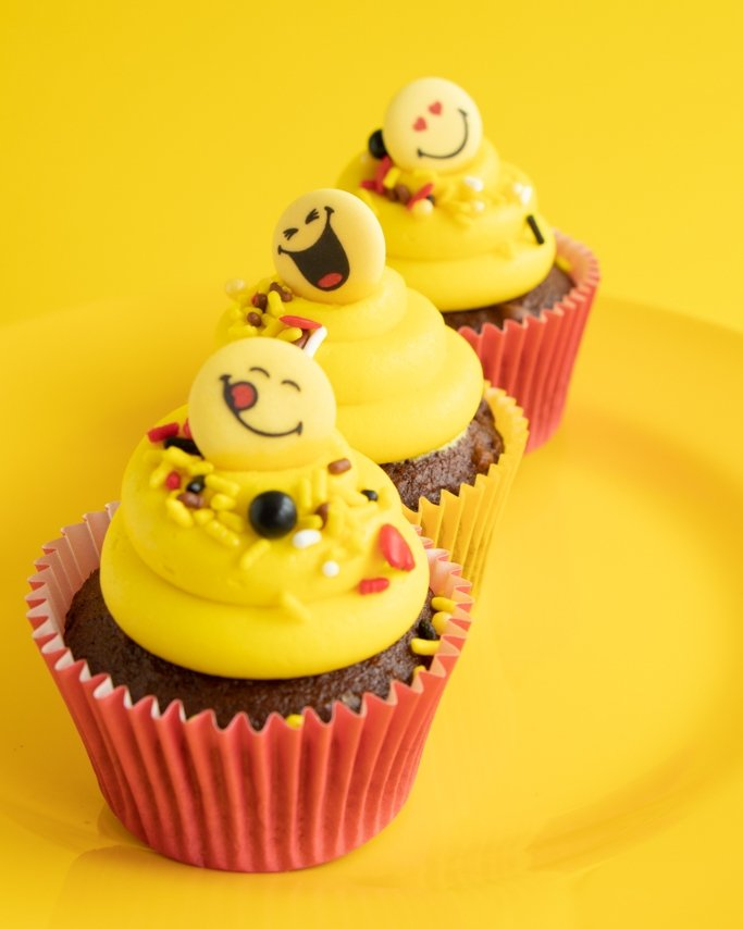 Emoji Cupcakes with Emoji sprinkles in red greaseproof cupcake liners on yellow background