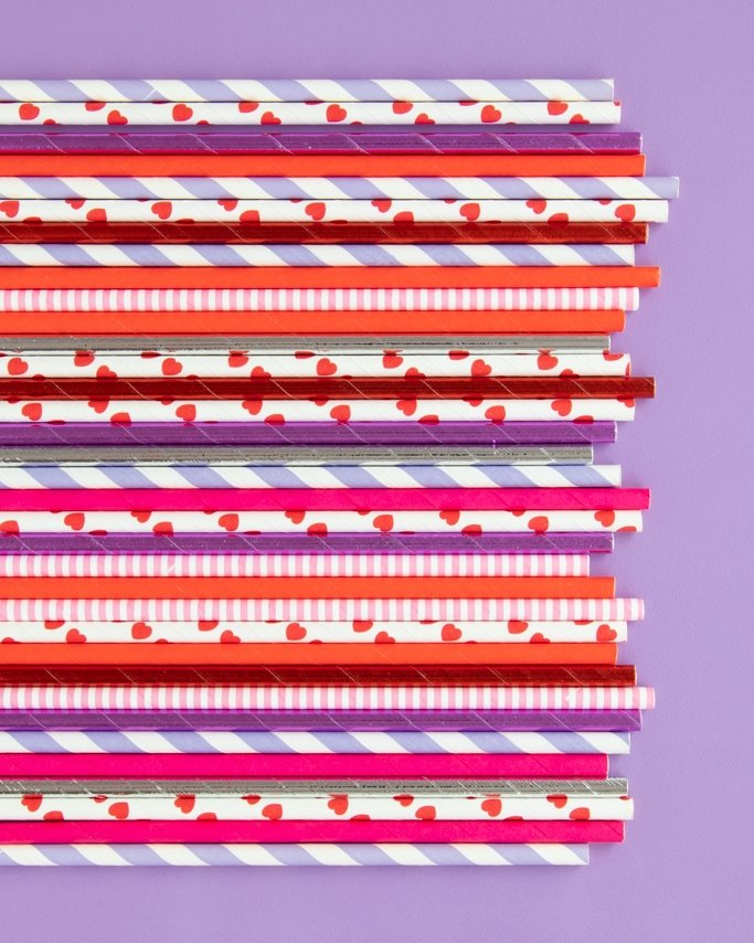 Pink and Purple Valentine Paper Straws on purple background