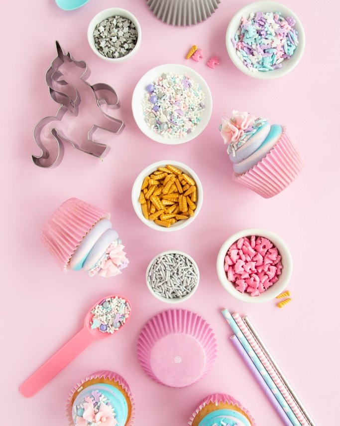 Unicorn Party Supplies flatlay with unicorn sprinkles and other unicorn party ideas with pastel party supplies