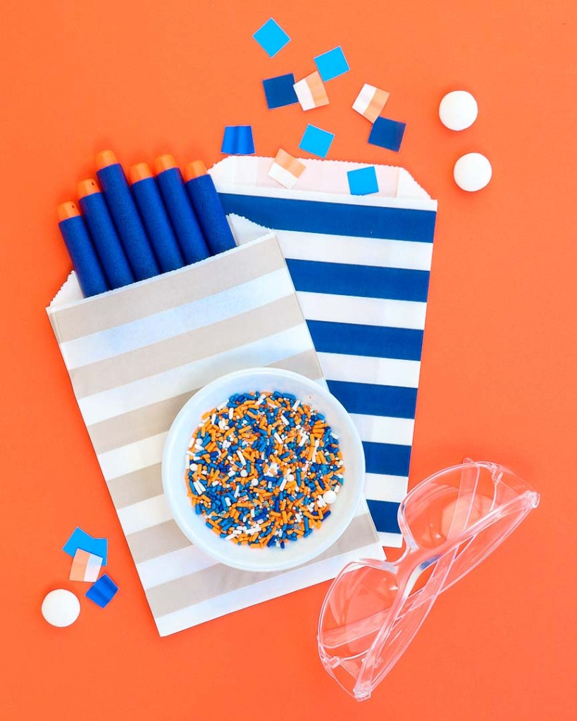 Goodie bags and table confetti on orange background with nerf darts and safety glasses