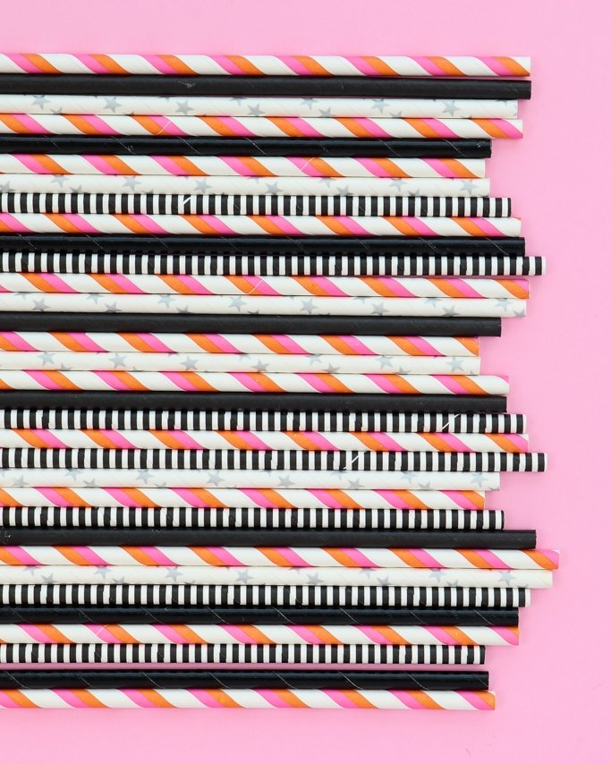 Glamoween Halloween Party Paper Straws in assorted patterns on pink background